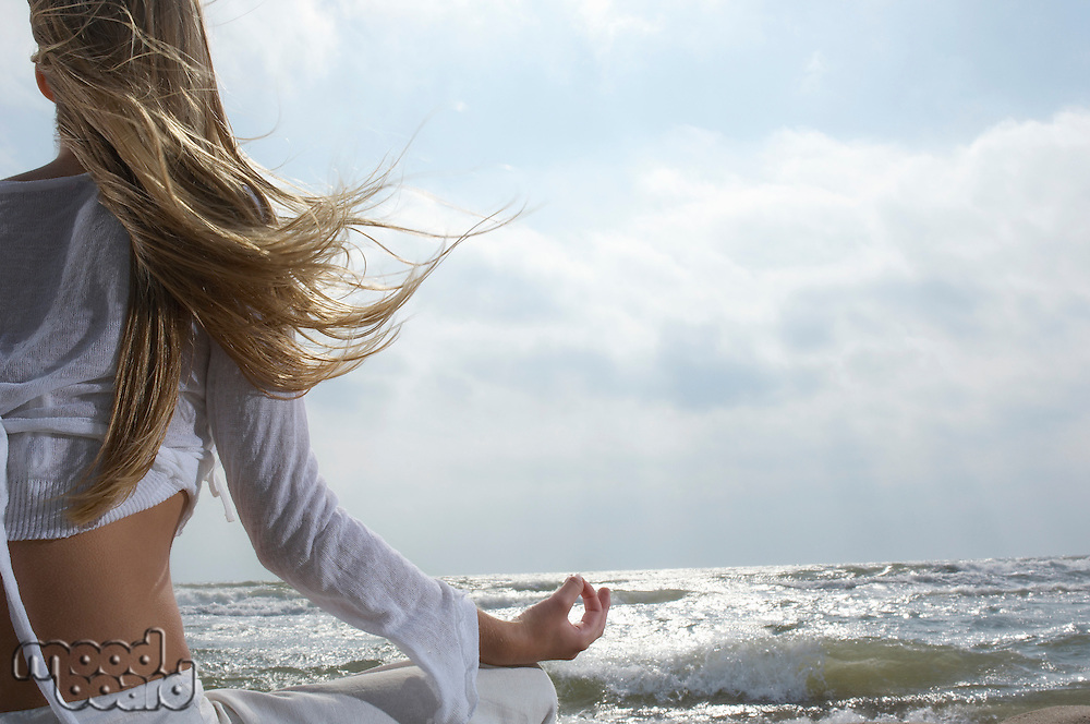 Young woman meditating on beach facing ocean back view