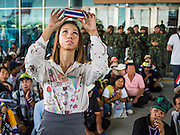 """08 APRIL 2014 - BANGKOK, THAILAND: A Ministry of Justice employee uses her iPhone, which has a case modeled on the Thai flag, to photograph anti-government protestors in front of the Ministry. Several hundred anti-government protestors led by Suthep Thaugsuban went to the Ministry of Justice in Bangkok Tuesday. Suthep and the protestors met with representatives of the Ministry of Justice and expressed their belief that Thai politics need to be reformed and that corruption needed to be """"seriously tackled."""" The protestors returned to their main protest site in Lumpini Park in central Bangkok after the meeting.    PHOTO BY JACK KURTZ"""