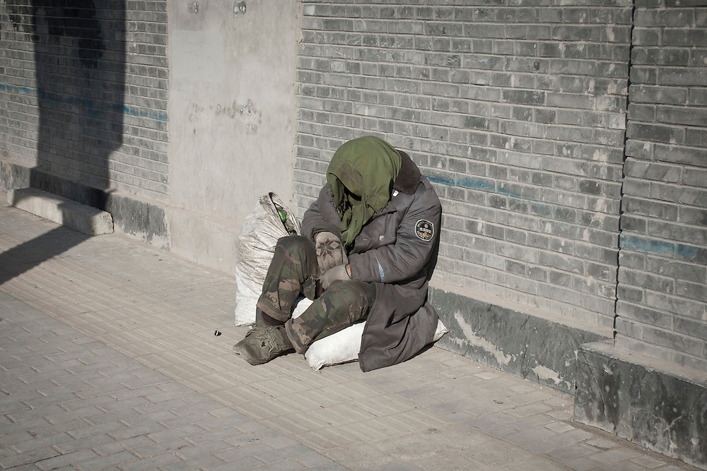 A homeless man in the streets of Beijing, near the Houhai lake, Di'anmen avenue. Winter 2011.