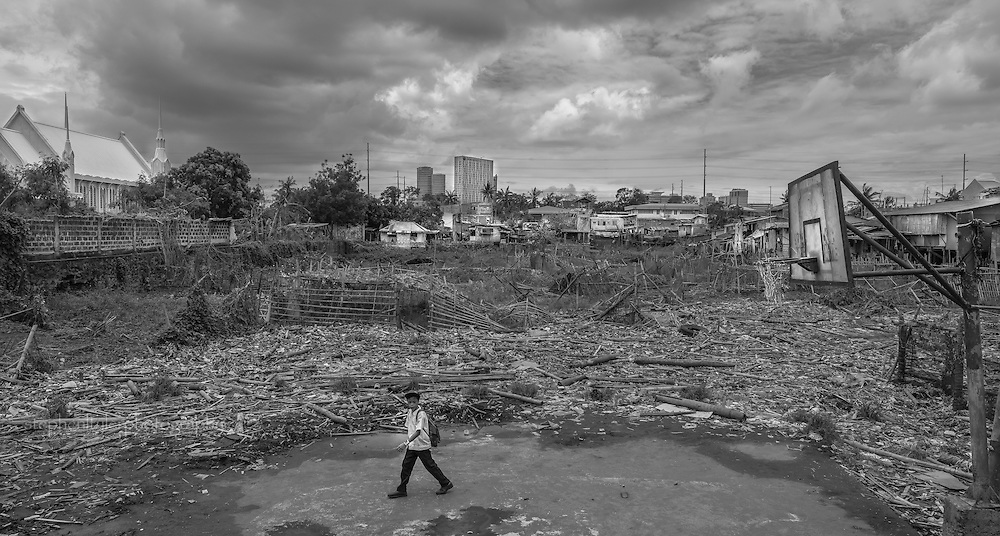 Everyday life in a fishing village community with nearly everything built from bamboo on top of stilts on the edge of a lake. A boy walks through a partially trashed basketball court on his way home from school