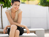 Smiling woman sitting on bench in plaza portrait