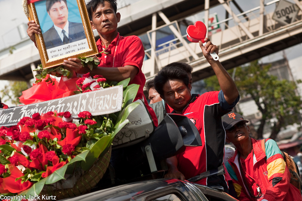 Apr. 12, 2010 - BANGKOK, THAILAND: Mourning Red Shirts hold up the photo of a man killed Saturday during the funeral procession in Bangkok Monday. The funeral cortege for the Red Shirts killed in the violent crackdown Saturday wound through Bangkok Monday. Thousands of mourners came out to pay respects for dead Red Shirts. 21 people, including 16 Thai civilians were killed when soldiers tried to clear the Red Shirts' encampment in Bangkok. Thousands more came out to call for the government of Thai Prime Minister Abhisit Vejjajiva to step down. Today Gen. Anupong Paojinda, the Chief of Staff of the Thai Army, reiterated that the Army would not use violence to break up the protests and joined the call for the Prime Minister to call new elections. This is the beginning of Songkran, Thai New Year's week, and the government has cancelled the official festivities fearing more violence. It was during last year's Songkan festivities that the Thai Army and police used force to break up the Red Shirt protests. That protest is now called the Songkran Riots.     Photo By Jack Kurtz