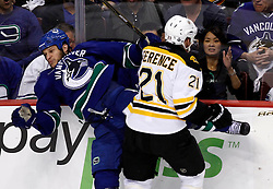 June 1, 2011; Vancouver, BC, CANADA; Vancouver Canucks defenseman Kevin Bieksa (left) is checked by Boston Bruins defenseman Andrew Ference (21) during the first period in game one of the 2011 Stanley Cup Finals at Rogers Arena. Mandatory Credit: Jason O. Watson / US PRESSWIRE