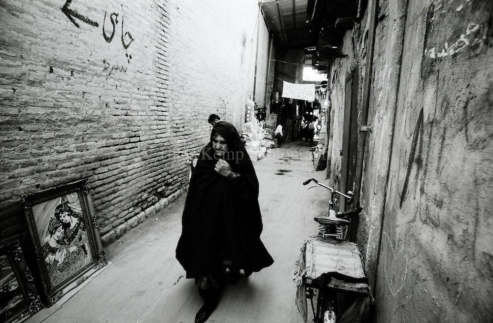 A woman walks through an alley in the city of Rasht, Iran, 1997
