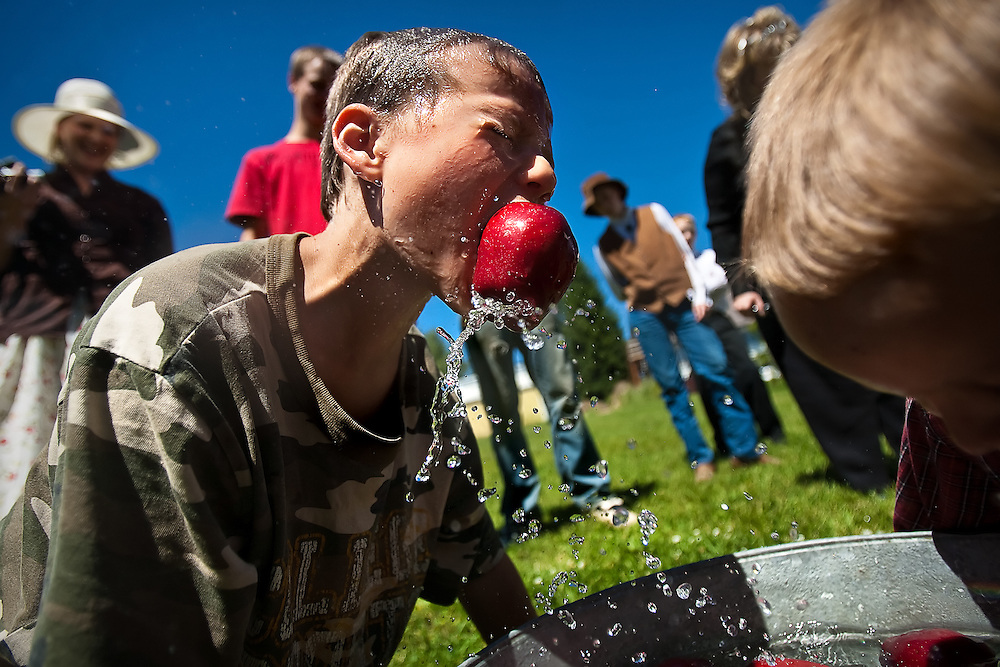 Robert Sperber of Plummer triumphantly pulls his apple out of a tin bucket during a game of bobbing for apples at the Plummer Bible Church's 100th anniversary celebration on Sunday.
