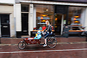 Een vrouw rijdt met een bakfiets met kinderen door de regen in Utrecht.<br /> <br /> A woman is cycling in the rain on a cargo bike with children in Utrecht.