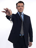 one caucasian realtor man real estate agent businessman teasing holding offering keys isolated studio on white background