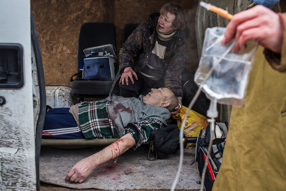 A man injured by shelling is tended to by his wife as he arrives at a polyclinic in the back of a van, where he will be transferred to an ambulance to be taken to a hospital on January 28, 2015 in the Petrovskyi district of Donetsk, Ukraine. The area, in the city's southwest, is close to heavy front-line fighting in Marinka.