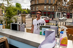 Pictured: Barman Marco Iroldi ready to serve refeshments on a sunny day<br /> <br /> Pubs are having to be imaginative during lockdown to keep their customers satisfied.  McLarens on the Corner in Edinburgh, former bank at Holy Corner, have brought in a converted Winneibago to provide hot meals and snacks, with a counter for beer drinks, cocktails and slushies for customers to take home and enjoy.  The bar does not have a license to allow drink to be consumed in the forcourt so they have arranged for drinks to be taken home in branded containers.