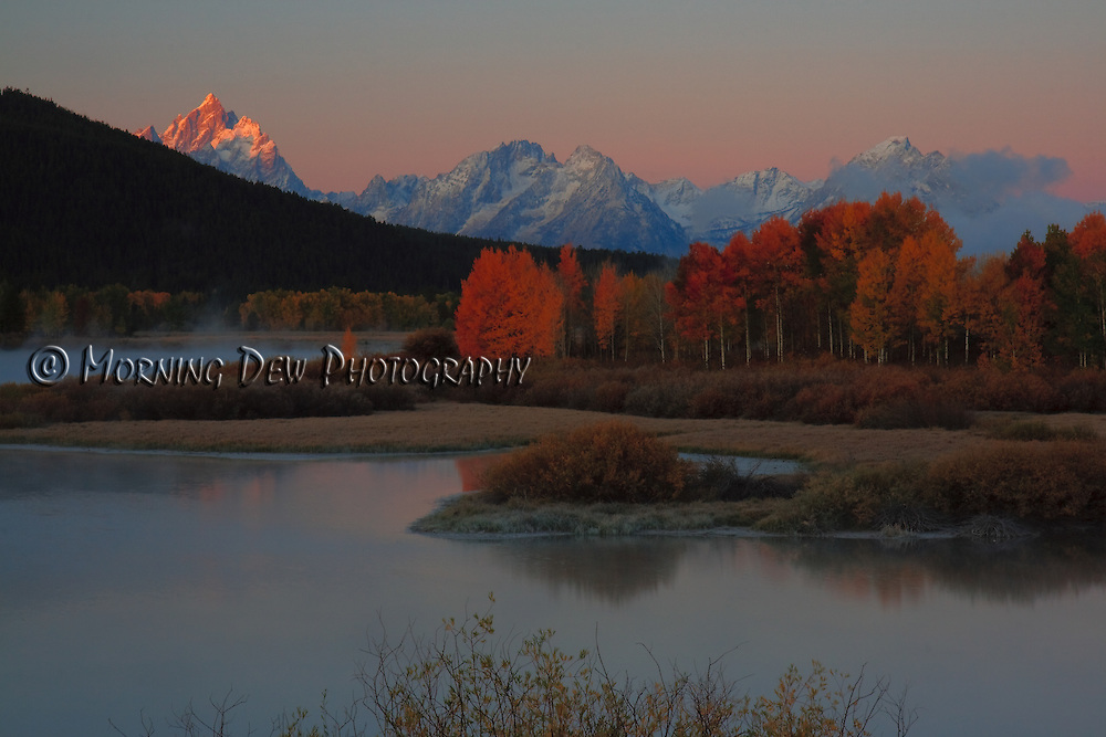 A fog lifts from the Snake River as the first rays of sun light the peaks of the Grand Teton mountains.