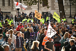 © Licensed to London News Pictures. 08/10/2019. London, UK. Police move in on Extinction Rebellion activists on Whitehall, outside Downing Street in an attempt to move them to Trafalgar Square. Activists have converged on Westminster for a second day, blockading roads in the area and calling on government departments to 'Tell the Truth' about what they are doing to tackle the Emergency. Photo credit: Ben Cawthra/LNP