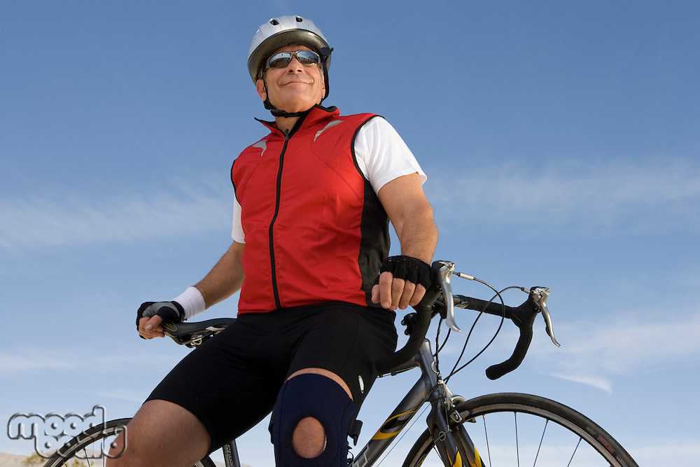 Senior man leaning on bike