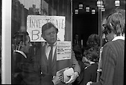 Fergus Rowan sits in at Bank of Ireland.  (J70)..1975..22.08.1975..08.22.1975..22nd August 1975..As a result of the 1970 bank strike which lasted for six months, the Rowan family business found itself in financial difficulties. During the strike the Rowans had had to accept cheques in good faith in order to stay in business. When the cheques came for settlement the bank refused as they stated that some were 'dodgy'. This put severe strain on the business which was eventually put into receivership.As part of the process the Rowan business beside the bank was put up for sale and was purchased by B.o I. Rowan was outraged and started a campaign against the bank which culminated in a sit in at the banks headquarters in Westmoreland St,Dublin. He also became a thorn in the side of the bank at the A.G.Ms raising many points...Image of bank officials struggle to prevent Fergus Rowan allowing his supporters and family entering the bank.