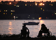 Beacon, New York - Two people, including one woman in a wheelchair, sit by the Hudson River at twilight on July 4, 2010. ©Tom Bushey / The Image Works