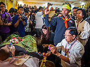 27 JANUARY 2014 - BANGKOK, THAILAND:  Anti-government activists and protestors chant political slogans during bathing rites for Suthin Taratin at Wat Sommanat Rajavaravihara in Bangkok. In Thai tradition, after death a bathing ceremony takes place in which relatives and friends pour water over one hand of the deceased. Suthin was a core leader of the People's Democratic Force to Overthrow Thaksinism (Pefot), one of several organizations leading protests against the elected government of Thai Prime Minister Yingluck Shinawatra. He was murdered Sunday, Jan. 28, while he was leading a rally to prevent voters from reaching a polling center in the Bang Na district of Bangkok.    PHOTO BY JACK KURTZ