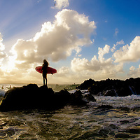 Silhouette of a surfer girl.