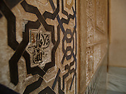 Arabic script and ornate geometric patterns tell of the Alhambra's Moorish past, inside the Palacios Nazaries, Granada (Andalusia), Spain.