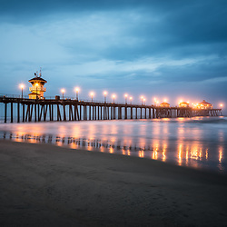 Picture of Huntington Beach Pier and dramatic blue storm clouds at night. Huntington Beach is a popular Orange County Southern California coastal city in the Western United States.