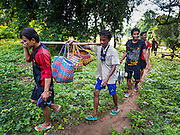18 JUNE 2016 - DON KHONE, CHAMPASAK, LAOS:  Fishermen carry their catch out of the Khon Pa Soi Waterfalls, on the east side of Don Khon. It's the smaller of the two waterfalls in Don Khon. Fishermen have constructed an elaborate system of rope bridges over the falls they use to get to the fish traps they set. Fishermen in the area are contending with lower yields and smaller fish, threatening their way of life. The Mekong River is one of the most biodiverse and productive rivers on Earth. It is a global hotspot for freshwater fishes: over 1,000 species have been recorded there, second only to the Amazon. The Mekong River is also the most productive inland fishery in the world. The total harvest of fish from the Mekong is approximately 2.5 million metric tons per year. By some estimates the harvest in the Tonle Sap (in Cambodia) had doubled from 1940 to 1995, but the number of people fishing the in the lake has quadrupled, so the harvest per person is cut in half. There is evidence of over fishing in the Mekong - populations of large fish have shrunk and fishermen are bringing in smaller and smaller fish.        PHOTO BY JACK KURTZ
