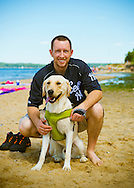 Sands Point, New York, U.S. - July 5, 2014 - During July 4th holiday weekend, people visit with their dogs to the Shoreline at Sands Point Preserve on the Gold Coast along Long Island Sound, when sunny warm weather arrives after a July 4th with many events canceled due to rain.