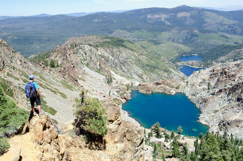 A hiker above the Pacific Crest Trail looking down on Young American and Sardine Lakes in Tahoe National Forest, California.