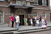Gasten zwaaien voor het stadhuis een bruidspaar uit.<br /> <br /> Guests are waving to a just married couple.