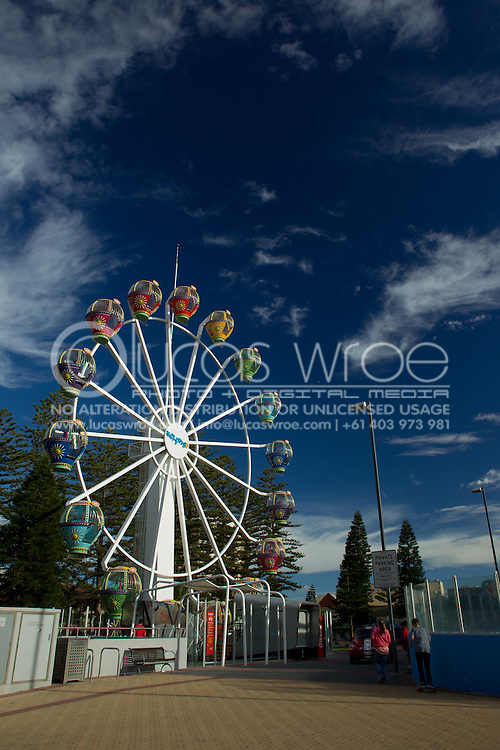 People walking past the Ferris Wheel. Glenelg, Adelaide, South Australia, Australia. 13/01/2012. Photo By Lucas Wroe.