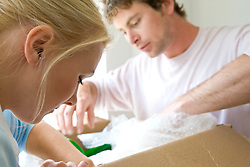 Close up of a young couple packing their belongings in a cardboard box