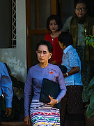"05 NOVEMBER 2015 - YANGON, MYANMAR: AUNG SAN SUU KYI leaves her home and walks to the press conference in her garden. During the press conference, which lasted 90 minutes, Aung San Suu Kyi, the leader of the National League for Democracy (NLD), said that if the NLD won the election she would serve ""above"" the President. When questioned about the Rohingya crisis in western Myanmar, a reporter called the situation ""dramatic"" and Suu Kyi replied the entire country is in a ""dramatic situation"" and the problems of the Rohingya should not be ""exaggerated."" She said the ""great majority of our people remain as poor as ever."" She also said the NLD would make a ""fuss"" if election results were ""suspicious."" Citizens of Myanmar go to the polls Sunday November 8 in what is widely viewed as the most democratic and contested election in Myanmar's history. The NLD is widely expected to win the election.   PHOTO BY JACK KURTZ"