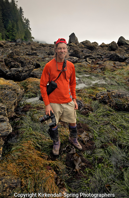 BC005500...BRITISH COLUMBIA - Photographer, Tom Kirkendall, on the rocky and rather slippery section of near Owen Point on the West Coast Trail in the Pacific Rim National Park.