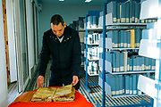 Al-Kairouine Mosque and University, Fez Medina, Morocco, 2018-02-02.<br /> <br /> Abdelfettah Bougchouf, the library's curator, reads from a 12th Century copy of 'the Miracle of Medicine' by Ibn Tufail, the only remaining copy in the world.  <br /> <br /> The Marinid dynasty expanded the Al-Karaouine library in 1359, adding a large space stacked with more than 20,000 hand-written books dating from the early Middle Ages. It also includes 4,000 rare texts and manuscripts.