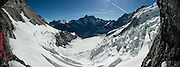 """From inside the east face of the Eiger at Eismeer Station (3159 m) of the Jungfraujoch Railway,  see the Schreckhorn (at center) and Eismeer Glacier (""""Sea of  Ice"""" in foreground), in Bern canton of Switzerland. Engineering the dramatic cog-wheel Jungfraujochbahn required 16 years (1898-1912) to carve through the Eiger and Mönch for 7 kilometers (4.3 mi), with gradients of up to 25%. Kleine Scheidegg entry station can be reached by trains from Grindelwald and Lauterbrunnen. The train ride from Kleine Scheidegg to Jungfraujoch (the highest railway station in Europe) takes 50 minutes including stops at Eigerwand and Eismeer viewing portals. Downhill return takes just 35 minutes. The Swiss Alps Jungfrau-Aletsch region is honored as a UNESCO World Heritage Site. This image was stitched from multiple overlapping photos."""