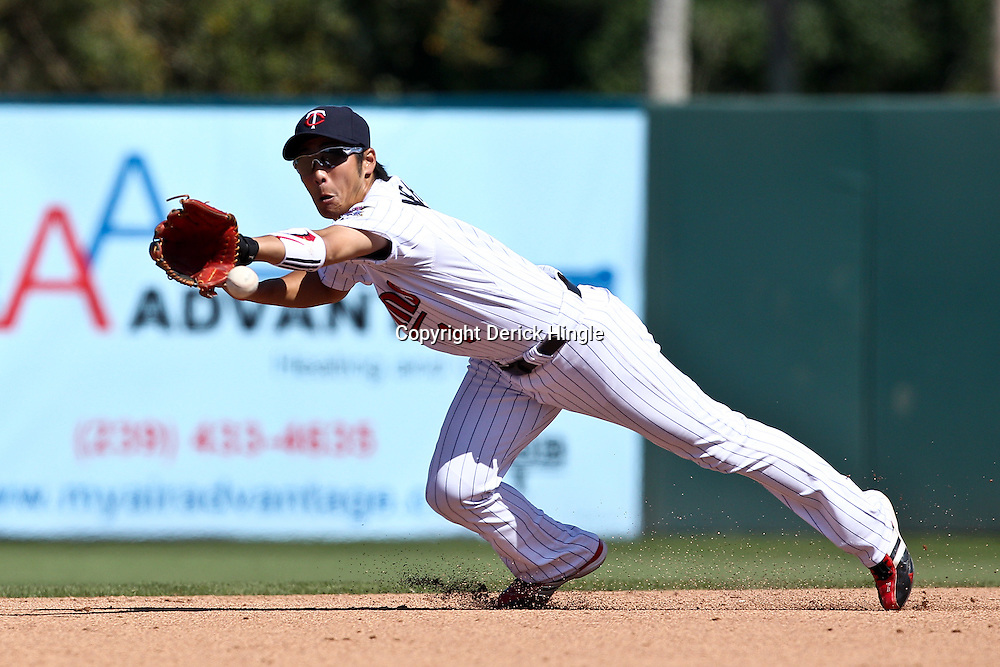 March 11, 2011; Fort Myers, FL, USA; Minnesota Twins second baseman Tsuyoshi Nishioka (1) makes a diving stop during a spring training exhibition game against the Boston Red Sox at Hammond Stadium.  Mandatory Credit: Derick E. Hingle-US PRESSWIRE