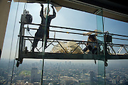 "Baiyoke 2 Tower, Bangkok's highest skyscraper, offers a splendid panoramic view over the ""City of Angels"". Window cleaners attaching a huge advertising poster."