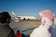 Dubai 2005, 9th International Aerospace Exhibition..First appearance of the new Airbus A380 in the Middle East and in the livery of its biggest buyer Emirates Airlines (45 planes ordered to date). Taxiing for takeoff. Sheik taking souvenir pix with his mobile phone cam. A Swedish JAS Gripen fighter performing in the background.