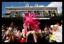 Feb 28th, 2006. New Orleans, Louisiana. Mardi Gras Day, Fat Tuesday. Crowds and faces in the crowd pack Chartres Street in the French Quarter for the annual St Anne's day parade, guaranteed to be awash with mainly locals out for an outrageous day out. A lady with a bright coloured head dress against a French Quarter background.