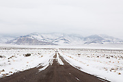 "An iced over dirt road leads to lonely and frigid mountains in the vast and barren expanse of Western Utah and Eastern Nevada. This road connects to Highway 50, the ""loneliest road in America."""