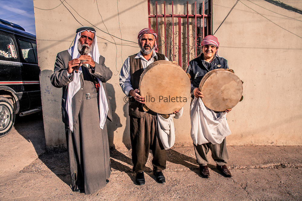 An old Kawal (left) with his son and his nephew playing the typical Yazidi instruments played at ceremonies: the Daf and the Shabbabi (flute)