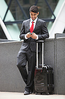 Young Indian businessman with luggage bag using cell phone