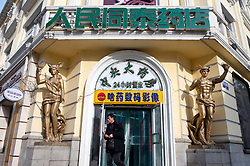 entrance to drugstore in Harbin China with ornate historic Russian decorative statues by door
