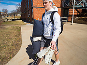 """13 MARCH 2020 - DES MOINES, IOWA: GAGE VANDERLEER, a first year student at Drake University, walks out to his car before going home for spring break. The Governor of Iowa announced Friday that 17 people in Iowa have tested positive for the Novel Coronavirus. Of those, 15 people were exposed on the same cruise in Egypt, the others were exposed through travel but were not on the same cruise. The Governor said there has not yet been any """"community spread"""" in Iowa. All of the Iowans who have tested positive are in self quarantine. Across Iowa, municipalities and businesses are taking steps to implement """"social distancing."""" Most of the colleges in Iowa, including Drake University, have announced that they will remain closed after their spring breaks and that classes will move to online only, after spring break. Many businesses in Des Moines, including Nationwide Insurance and EMC Insurance, have announced plans to have their employees to telecommute. The mayor of Des Moines has urged event planners to consider canceling large events.     PHOTO BY JACK KURTZ"""