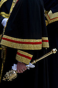 "A Beadle mace-bearer from the City of London holds a ceremonial mace in the crook of his left arm during the annual Lord""s Mayor's Show. We see only the arm and the golden mace as a close-up detail. The Beadle's role is now only symbolic, accompanying the City Adlermen as the lead the processions through the capital's ancient financial heart. A Beadle or bedel was a lay official of a church or synagogue who would usher, keep order, make reports, and assist in religious functions; or a minor official who carries out various civil, educational, or ceremonial duties. The term has Franco-English pre-renaissance origins, derived from the Vulgar Latin ""bidellus"" or ""bedellus"", rooted in words for ""herald"". It moved into Old English as a title given to an Anglo-Saxon officer who summoned householders to council."