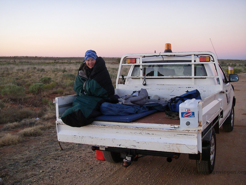 Woman using the back of an ute (Australian for utility vehicle) for camping