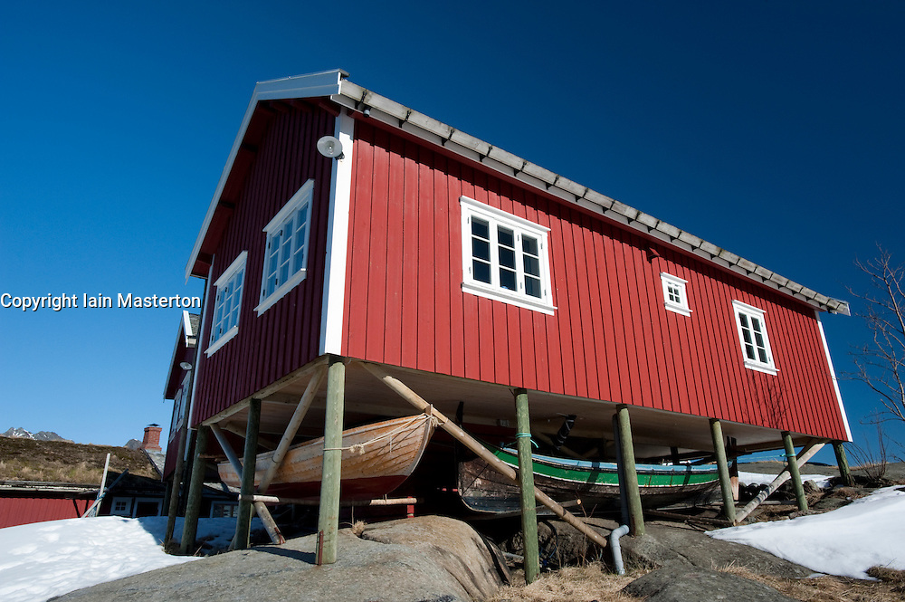 Traditional red wooden Rorbu fisherman`s hut with fishing boats stored below in village of Reine in Lofoten Islands in Norway