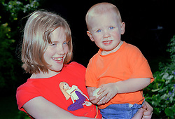 Young girl standing outdoors holding younger brother smiling,