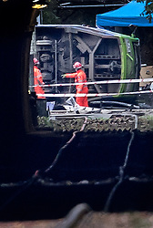 EDITOR'S NOTE: Photograph taken from a public area. © Licensed to London News Pictures. 09/11/2016. London, UK. Emergency workers inspect the underside of a derailed tram near Sandilands tram station in Croydon, Greater London. Dozens of people are believed to be injured with emergency services saying that there has been a number of fatalities. Photo credit: Peter Macdiarmid/LNP