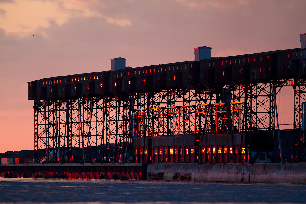 Canada, Manitoba, Churchill, Setting sun reflects off Port of Churchill's Grain Elevator Terminal along Hudson Bay