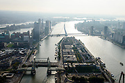 Nederland, Zuid-Holland, Rotterdam-Zuid, 28-09-2014; Nieuwe Maas met Noordereiland in tegenlicht. Gezien naar de Kop van Zuid en de Wilhelminakade met Erasmusbrug. Koninginnebrug en De Hef over de Koningshaven tussen Noordereiland en Rotterdam-Zuid.<br /> Rotterdam, river Nieuwe Maas (Meuse) in backlight. Bridges connecting the city centre (right) with the part south of the river (left), residential and former harbour areas.<br /> <br /> luchtfoto (toeslag op standard tarieven);<br /> aerial photo (additional fee required);<br /> copyright foto/photo Siebe Swart.