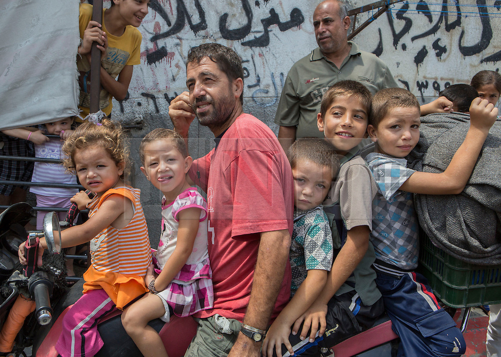 "© Licensed to London News Pictures. 15/07/2014. Gaza.  As the conflict entered it's eighth day news of a potential ceasefire reaches Gazan families who have been living in a UN school for the past 5 days.    The Al Fakoura school on the outskirts of the Bet Lahia district of Gaza has been home to over 600 families during the current Isreal/Gaza conflict known as Operation Protective Edge.<br /> <br /> The ceasefire calls came ahead of an urgent meeting of Arab League foreign ministers in Cairo. There are still no clear indications that a ceasefire has been agreed and although Israel have accepted the conditions,  however, the armed wing of Hamas, which controls Gaza, rejected the initiative as a ""surrender"".  Photo credit : Alison Baskerville/LNP"