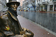 Lodz, Poland main street in the rain. (Piotrkowska St.) Brownze statue of Tuwims' Bench. (in memory of local poet Julian Tuwim.)